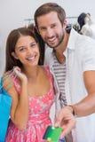支付由信用卡的微笑的夫妇画象  免版税库存照片