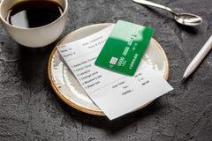 支付由信用卡的餐馆票据在黑暗的桌背景的咖啡 图库摄影