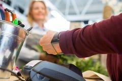 支付通过巧妙的手表的顾客在花店 图库摄影