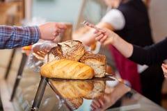 支付面包的顾客在面包店柜台 免版税库存图片