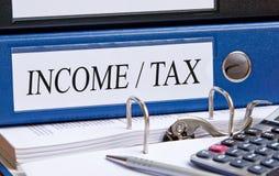 收入和税的蓝色黏合剂与文本在办公室 图库摄影