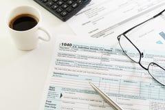 收入税单形式、咖啡,笔、计算器和玻璃 免版税库存图片