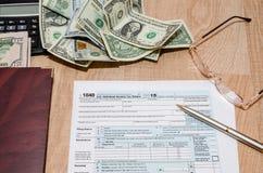 收入税单1040文件与计算器和美元的2016年 免版税库存照片