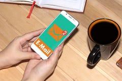 收到了一个电子邮件在网上在一个手机 妇女拿着在办公桌的背景的一个白色手机 免版税图库摄影