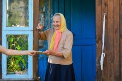 收到在门廊的资深妇女退休金钱在她的房子附近 祖母拿着金钱 免版税库存照片