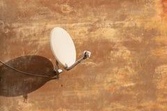 收到的数字电视信号卫星天线在涂灰泥的墙壁上 免版税图库摄影