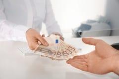 收到金钱的人从出纳在现金 免版税库存图片