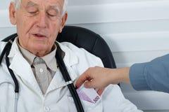 收到金钱的男性医生从患者 免版税库存图片