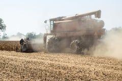 收割机切口烘干了,成熟的大豆搅拌尘土云彩在收割期 免版税库存图片