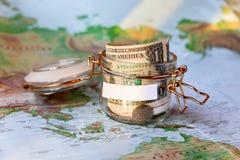 收旅行的金钱 作为moneybox的玻璃锡与现金 库存图片