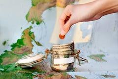 收旅行的金钱 作为moneybox的玻璃锡与现金 库存照片
