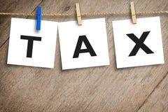 收税在招贴糊墙纸的消息与木背景 免版税库存照片