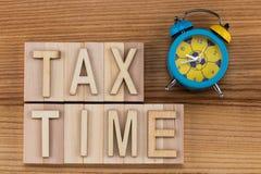 收税在葡萄酒信件的定期的文本在木块与警报 免版税库存照片