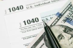 收税时间概念,在美元票据的笔与1040美国个体 库存图片