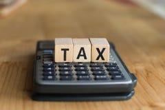 收税概念与在被堆积的硬币的木块,在背景的计算器 免版税库存图片