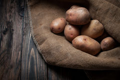 收获在粗麻布大袋的土豆在木背景 图库摄影