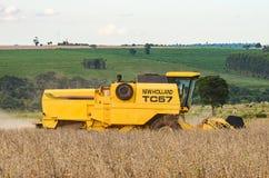 收获大豆种植园的拖拉机的边 库存照片