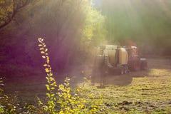 收获干草或草的拖拉机和打包机 免版税库存照片