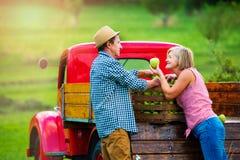 收获苹果的资深夫妇,站立在葡萄酒红色汽车 免版税库存图片