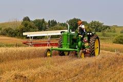 收获麦子的约翰Dere拖拉机和swather 图库摄影