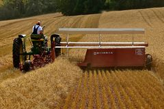 收获麦子的约翰Dere拖拉机和swather 免版税库存图片