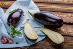 收获-成熟水多的茄子 与蓬蒿,大蒜叶子的茄子蓝色毛巾  裁减茄子在木厨房用桌上说谎 免版税库存图片