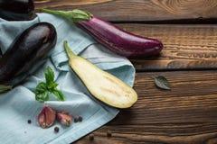 收获-成熟水多的茄子 与蓬蒿,大蒜叶子的茄子蓝色毛巾  裁减茄子在木厨房用桌上说谎 图库摄影