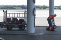 收集下落的行李的机场职员 图库摄影