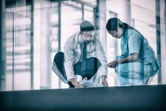 收集下落的医疗报告的医生和护士 免版税图库摄影