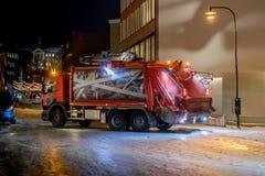 收集卡车的垃圾沿城市街道移动 黑暗的时刻 免版税库存照片