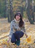 收集叶子的女孩在秋天森林里 库存照片
