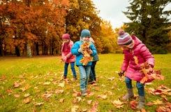 收集叶子的小组孩子在秋天公园 免版税库存图片