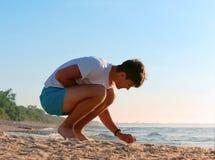 收集在海岸的石头,男孩收集在海,基于沿海的年轻人的石头 库存照片