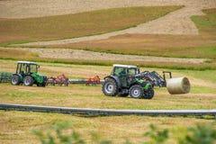 收集在草甸的拖拉机新鲜的干草在阿尔卑斯 免版税库存照片