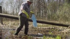 收集垃圾的资深妇女志愿者在池塘 影视素材