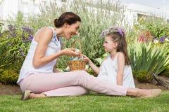 收集复活节彩蛋的母亲和女儿 库存照片