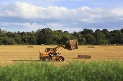 收集干草堆的拖拉机从领域 免版税库存照片