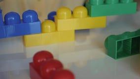 收集开发的设计师lego的男孩` s手的特写镜头坐在白色桌上 概念的愉快 影视素材