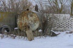 收集的牛奶一辆大坦克在石篱芭附近 免版税库存照片