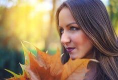收集秋天叶子的可爱的少妇 免版税库存图片