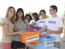 收集衣物捐赠的组志愿者 免版税库存照片