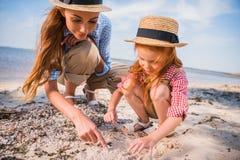 收集贝壳的母亲和女儿 图库摄影