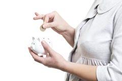 收集金钱概念 妇女特写镜头在白色背景隔绝的存钱罐中投掷硬币 银行票据贪心放置的节省额 免版税图库摄影