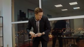 收集金钱现金的快乐的商人从在平衡办公室的桌面 股票录像