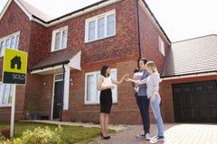 收集钥匙的年轻家庭对新的家从地产商 库存照片