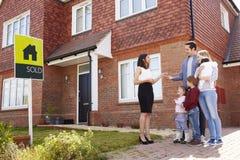 收集钥匙的年轻家庭对新的家从地产商 免版税库存照片