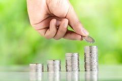 收集银币的金钱增加金钱人` s手筹集长大企业自然背景的金钱 免版税库存图片