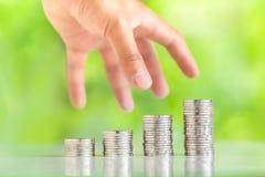 收集银币的金钱增加金钱人` s手筹集长大企业自然背景的金钱 免版税库存照片