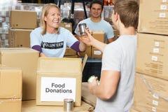 收集食物捐赠的志愿者在大商店里 免版税库存照片