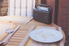 收音机和残羹剩饭在桌上 免版税图库摄影